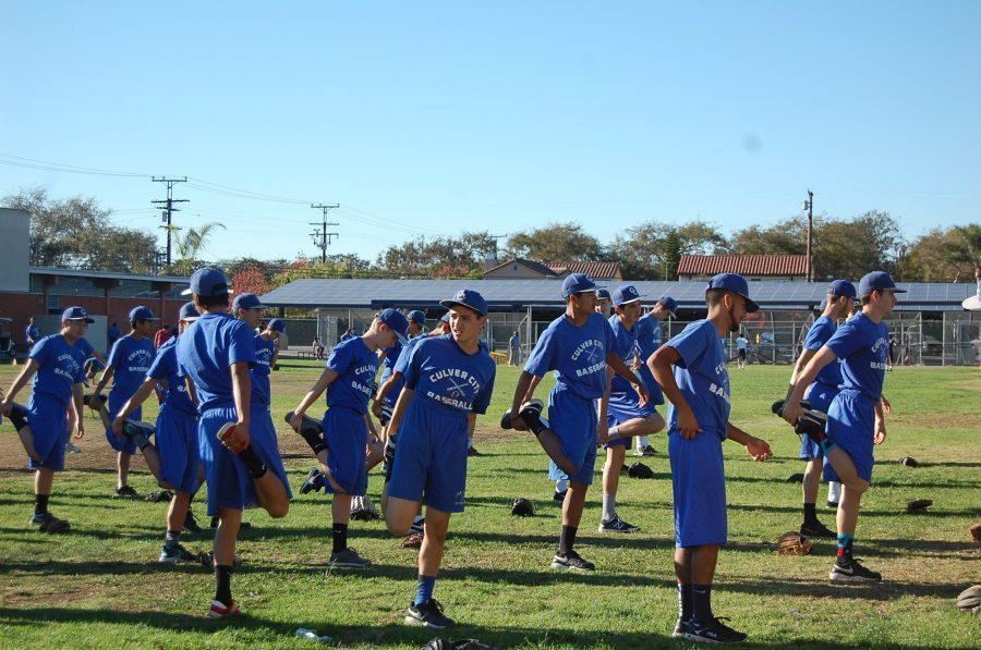The baseball team stretches on the practice field while regular field is being renovated.